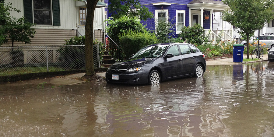 car parked in standing water on flooding street
