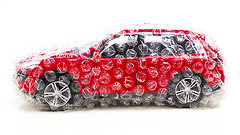 red toy car wrapped in bubble wrap