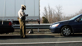 police officer writing ticket pulled over driver