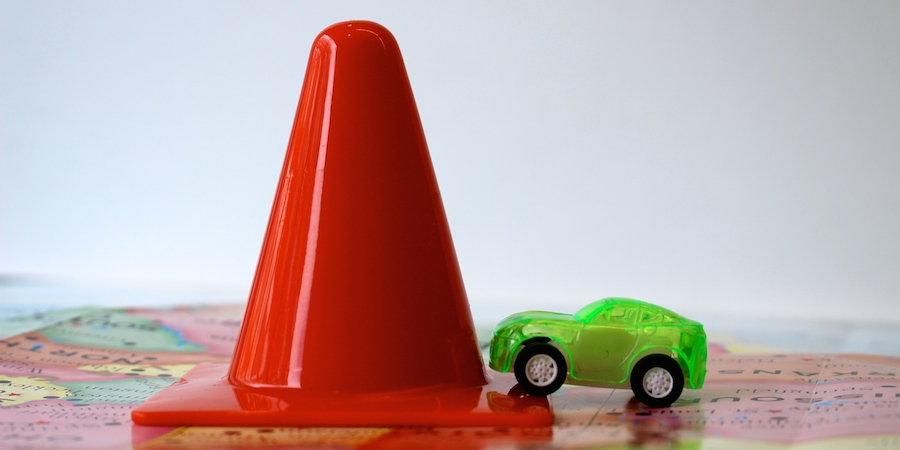 green car with traffic cone on map
